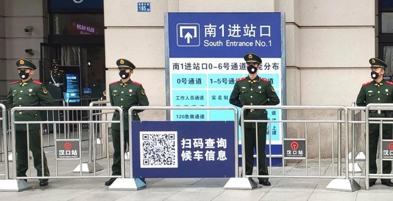 Сотрудники полиции охраняют вход на закрытый железнодорожный вокзал Ханькоу в городе Ухань, Китай, в четверг 23 января 2020